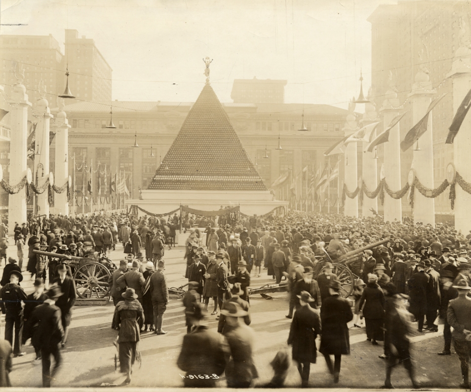 """View of the employees of the New York Central Railroad, assembled in Victory Way, showing the pyramid of captured German helmets, with Grand Central Terminal in the background."""